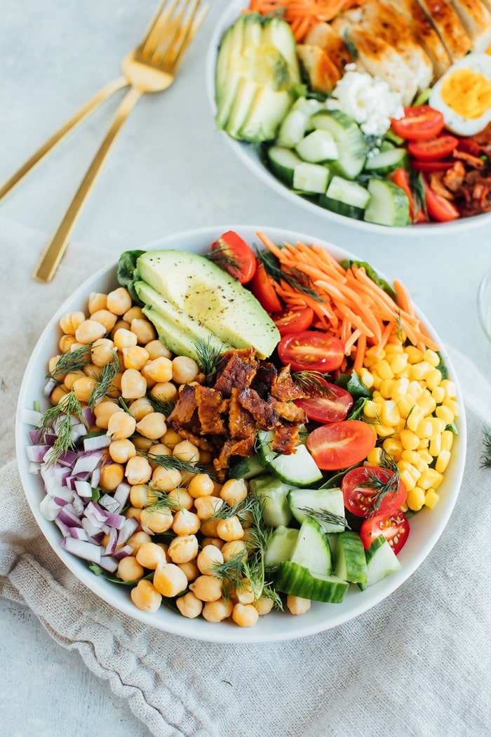 Vegan cobb salad in a white bowl with two gold forks in the background.