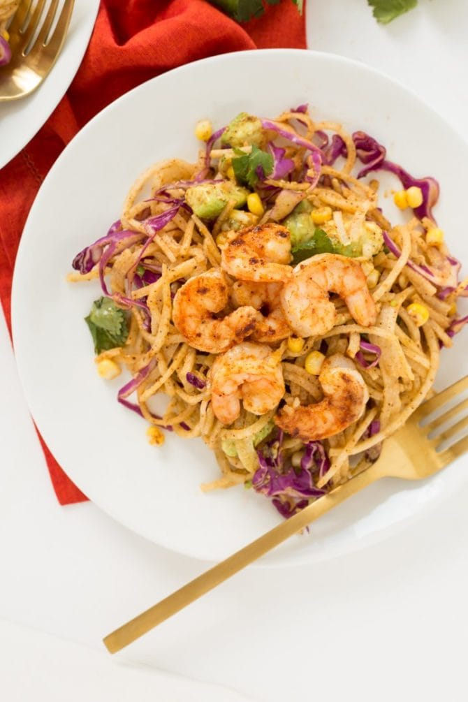 Chili lime shrimp and corn on top of a plate of spiralized jicama noodles. A gold folk in resting on the plate.