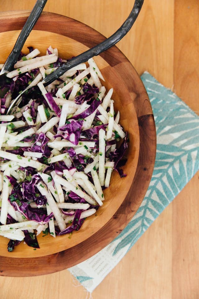 Wooden bowl filled with jicama and purple cabbage slaw with two metal serving spoons.