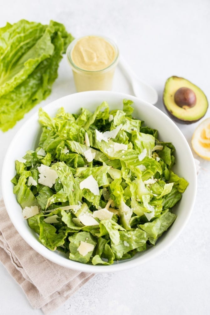 Bowl filled with romaine lettuce. Next to the bowl is a head of lettuce, a jar of avocado caesar dressing, and a half avocado.