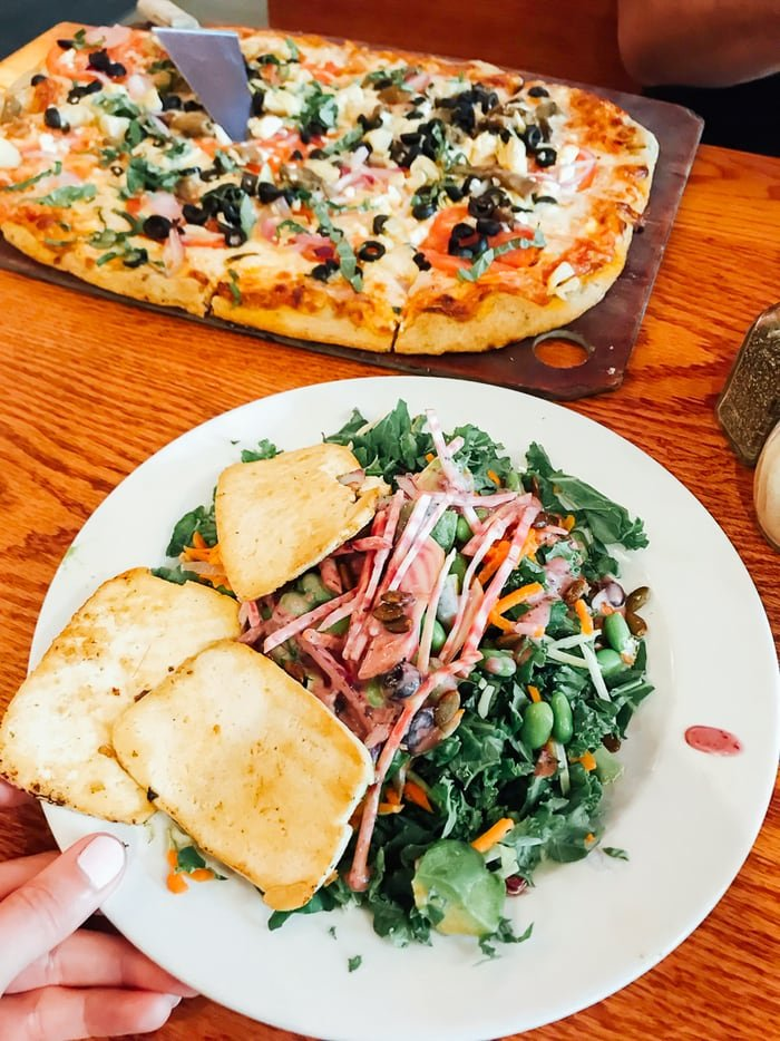 Salad and a pizza on a wooden table.