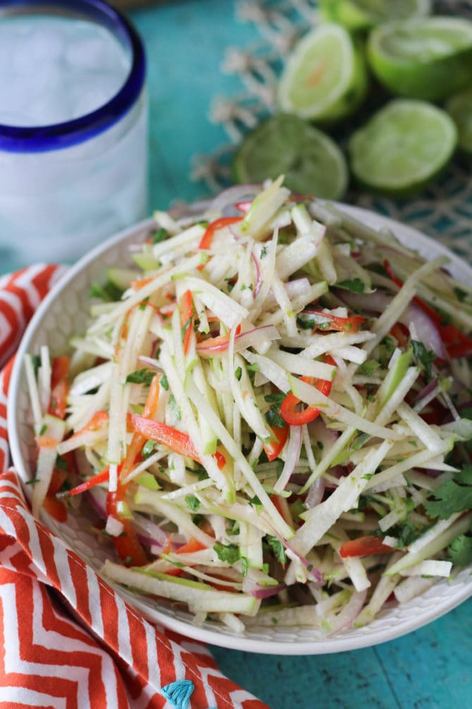 Jicama and apple slaw in a bowl next to a water glass and a bunch of limes.