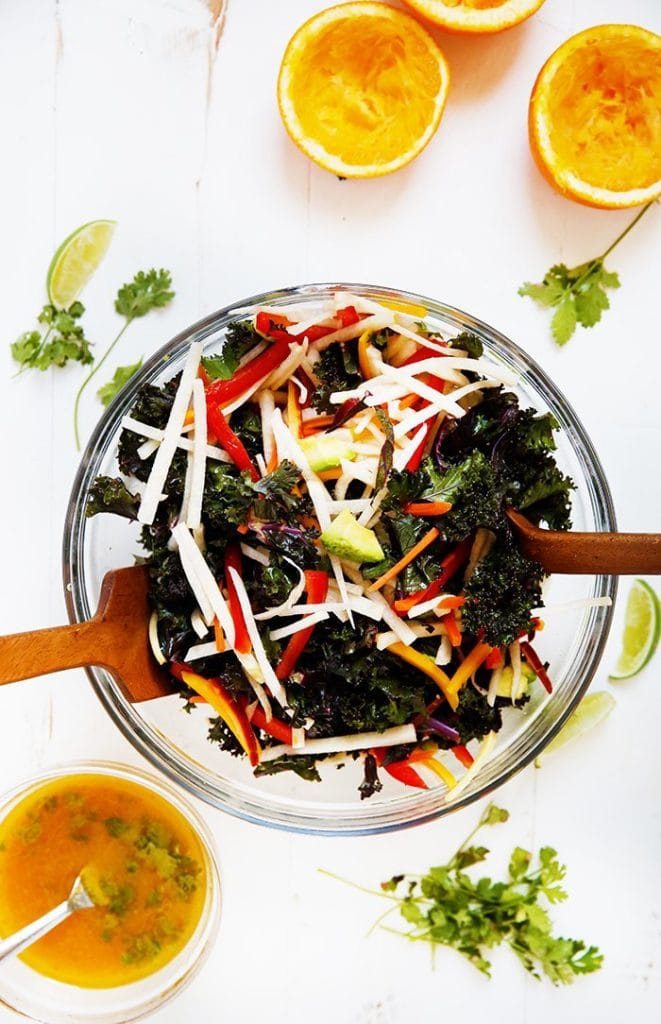 Glass bowl with kale salad with oranges and herbs on the table. The salad has jicama and colorful veggies.
