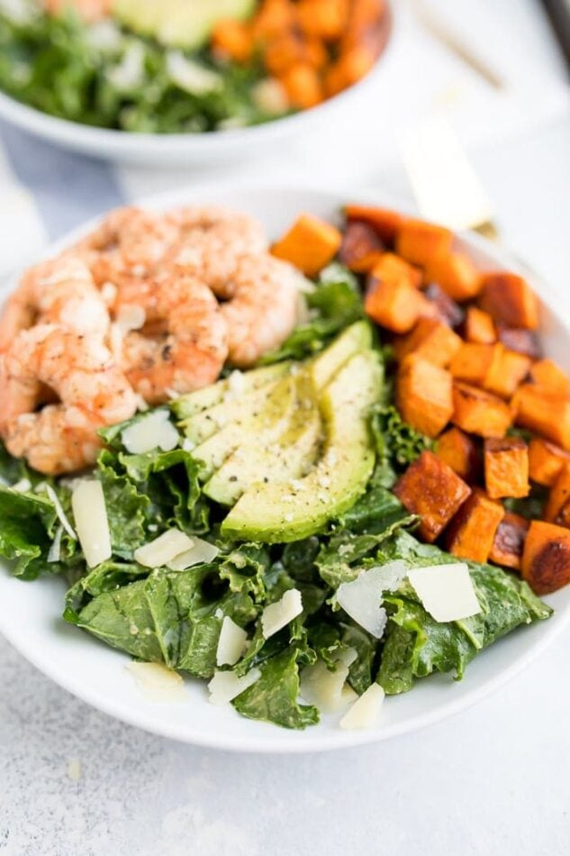 Kale caesar salad topped with grilled shrimp, avocado, sweet potatoes and parmesan cheese shavings in a white bowl.