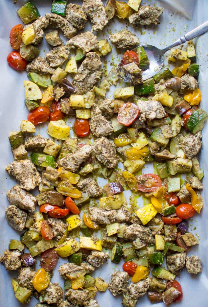 Sheet pan with parchment paper, with baked pesto chicken and tomatoes, zucchini and summer squash.