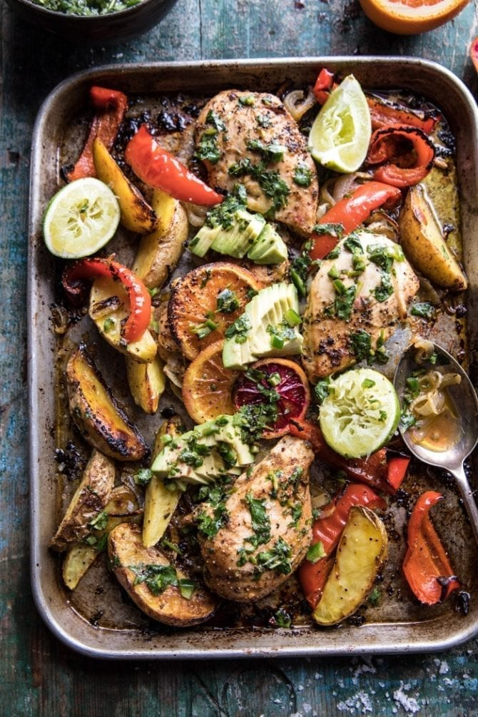 Sheet pan with baked chicken, peppers, potatoes, avocado slides and lime halves.