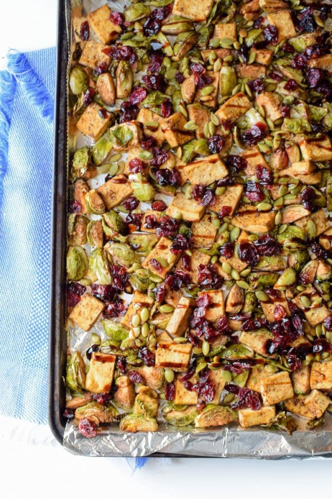 Sheet pan with baked garlic tofu and Brussels topped with pumpkin seeds and craisins.