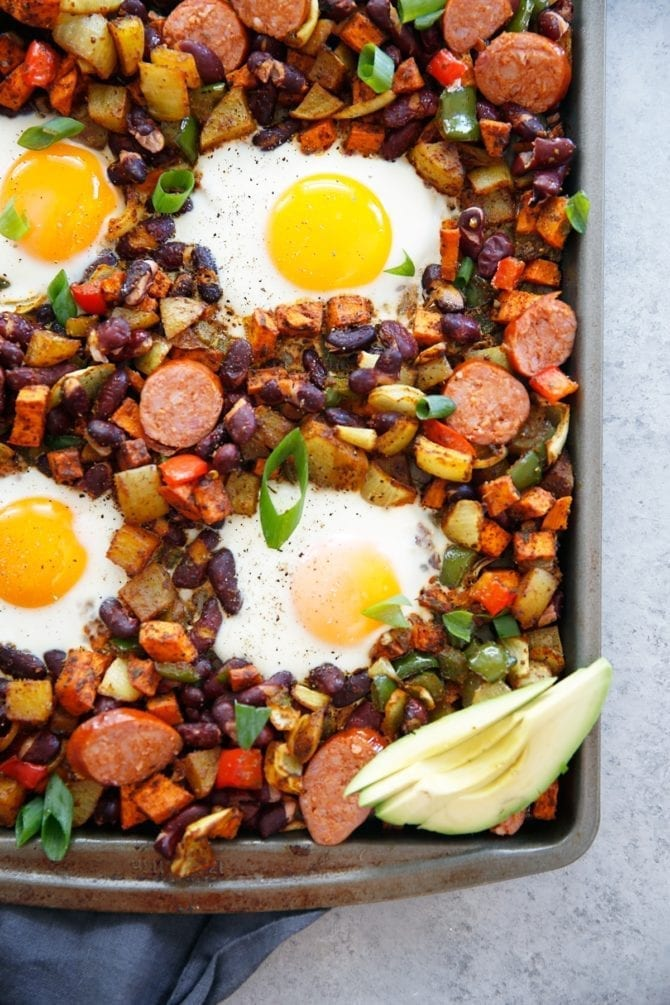 Sheet pan meal with chorizo, eggs, beans, avocado and onions.