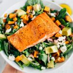 Seared wild-caught salmon over salad with sweet potato croutons, feta, avocado and pickled red onions.