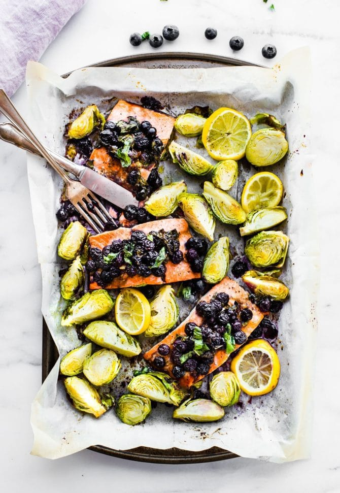 Sheet pan with parchment paper and silverware. Salmon baked with blueberries on top, Brussels sprouts and lemon.