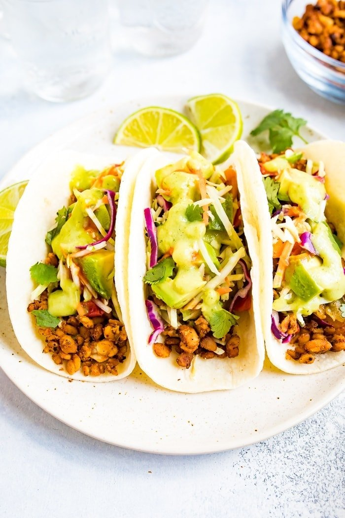 Three tempeh tacos with avocado and tomatillo dressing on a plate.
