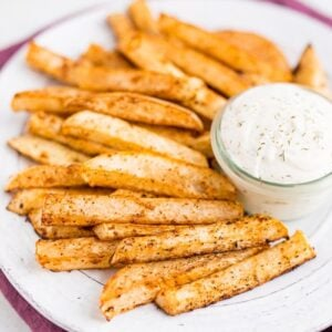 A white plate of turnip fries and a jar of ranch dip on top of a purple napkin.