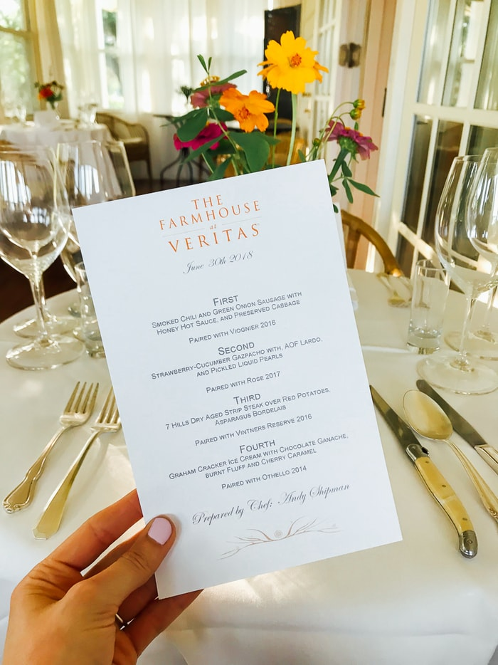 Dinner menu from The Farmhouse at Veritas with four courses. Hand holding menu with table set with silverware and flowers in the background.
