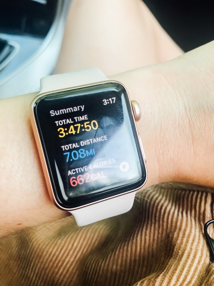 Apple Watch on a wrist showing a hike time of 3:47, distance of 7.08 miles, and active calories 662.