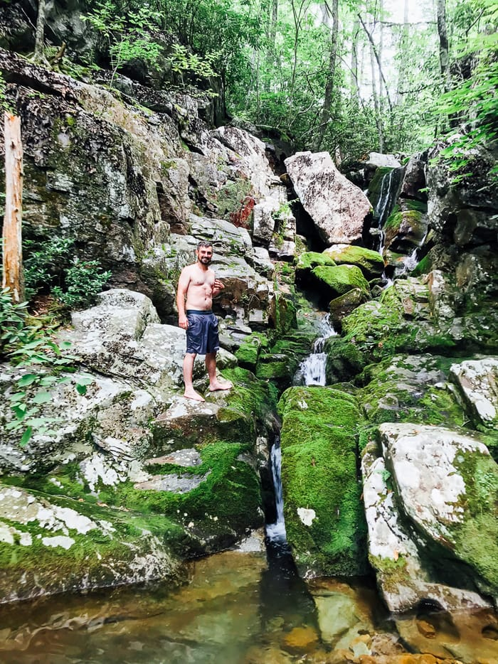 Man standing on a mossy rock, about to jump into the swimming hole in the mountains.