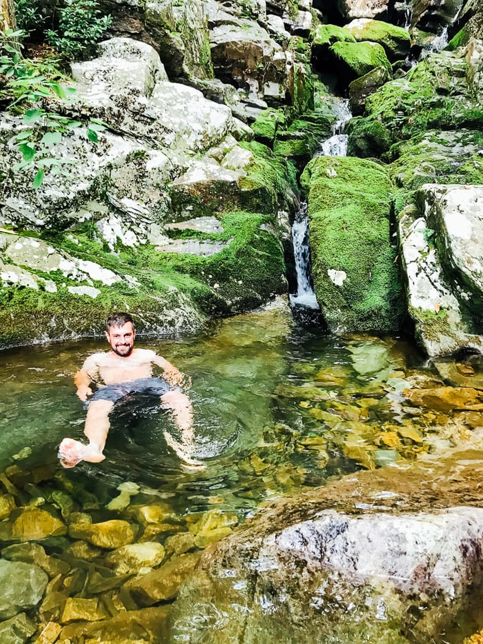 A man sitting in a natural spring in the Blue Ridge Mountains. Moss on rocks, and a small waterfall goes into the swimming hole.