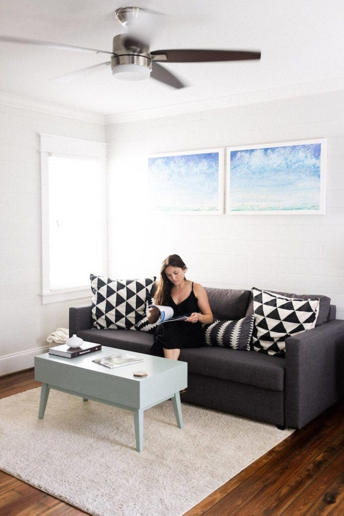 Woman sitting on a couch looking as a magazine. There is a coffee table, a rug and a couple paintings in the room. A window is beside her. The room is very clean and minimalist.