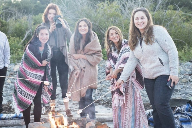 A group fo 5 woman roasting marshmallows on a beach, wrapped in patterned blankets.