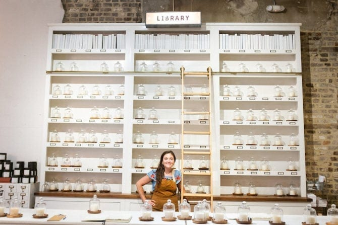 "Woman wearing an apron and standing in front of a wall filled with shelves of candle waxes. A sign says ""library""."