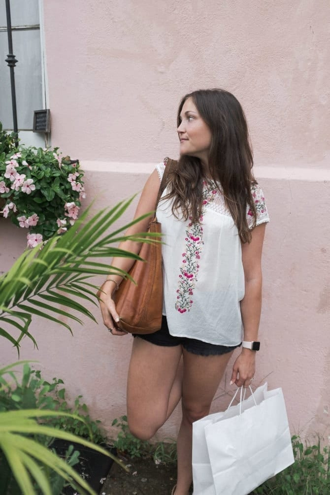 Woman holding a purse and a shopping back and standing in front of a pink wall. Flowers and palms grow by the wall. She is wearing an embroidered top and shorts.