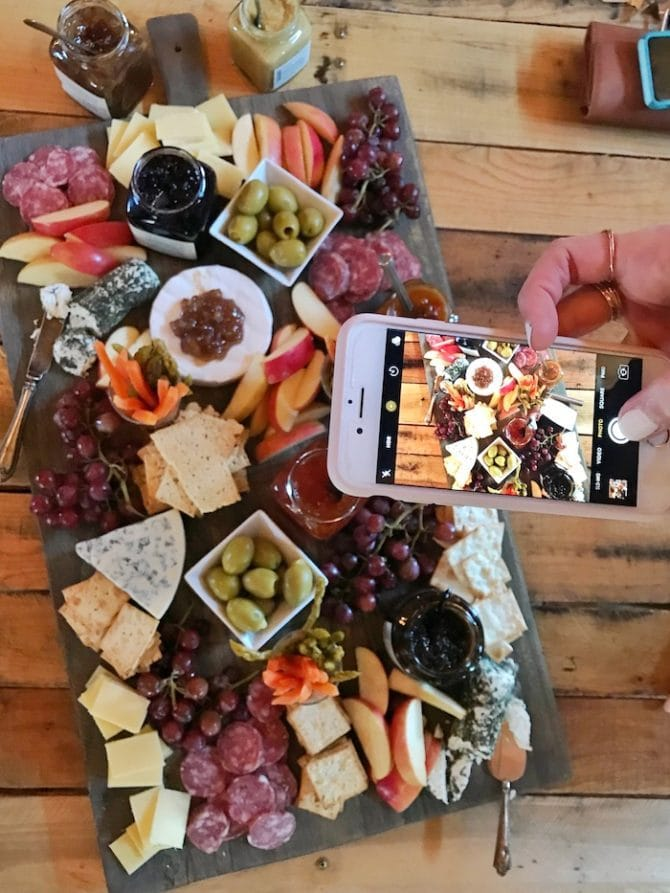 Woman taking a iPhone photo of a cheese, meat, and fruit platter.