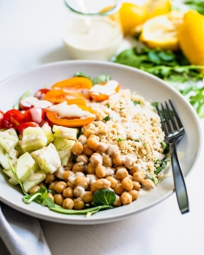 Chickpea Couscous Bowls -- bowls with cucumber, chickpeas, couscous and tomatoes on greens.