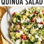 Bowl of quinoa salad with feta, spinach and tomatoes.