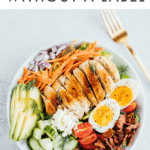 """Photo of a chicken Cobb salad, with avocado, onion, carrots, cucumber, egg, tomatoes, and bacon. Text reads """"healthy Eating without a Label"""""""