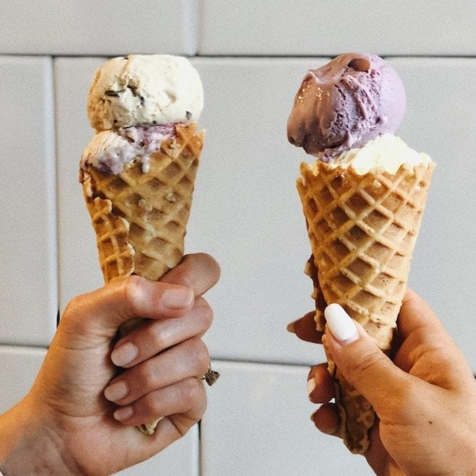 Two women's hands holding cones from Jeni's ice cream in Charleston, SC.