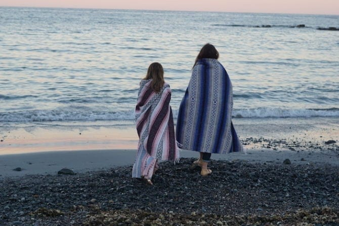 Two women holding patterned blankets around themselves, walking barefoot on a pebble beach in Maine.