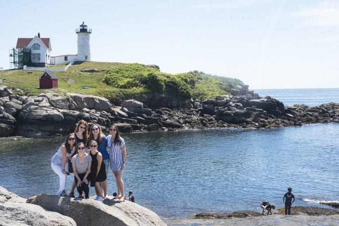 A group of 6 women posing on a rock in front of Nubble Lighthouse in Maine. The coast is rocky and filled with grass. The lighthouse and house next to it look over the sea.