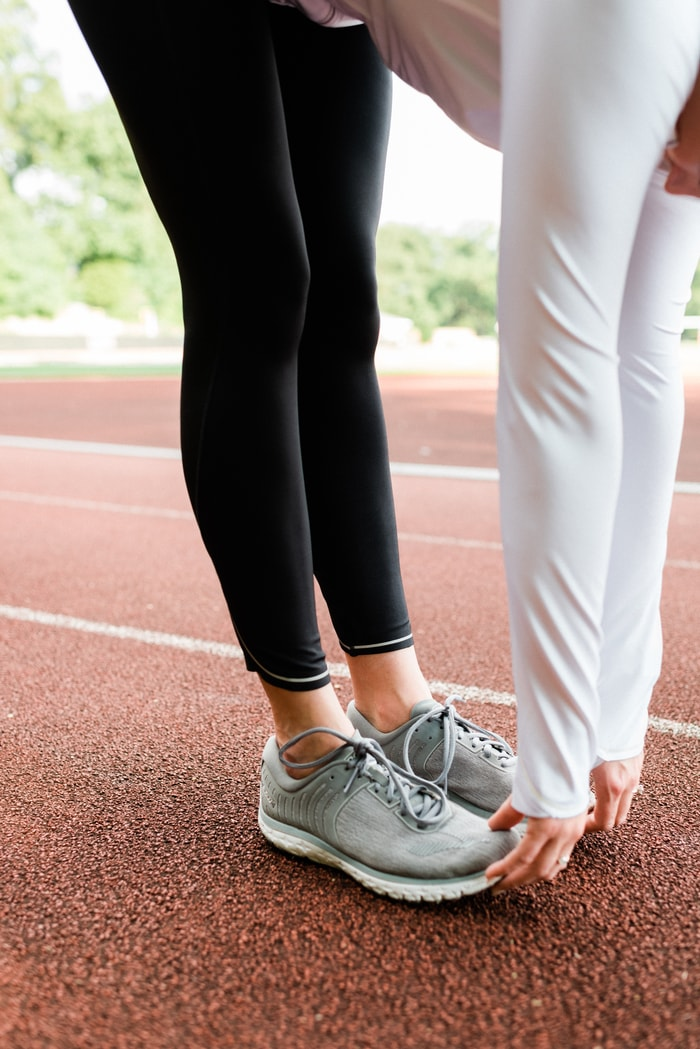 Women stretching on track with black running tights and white running jacket.