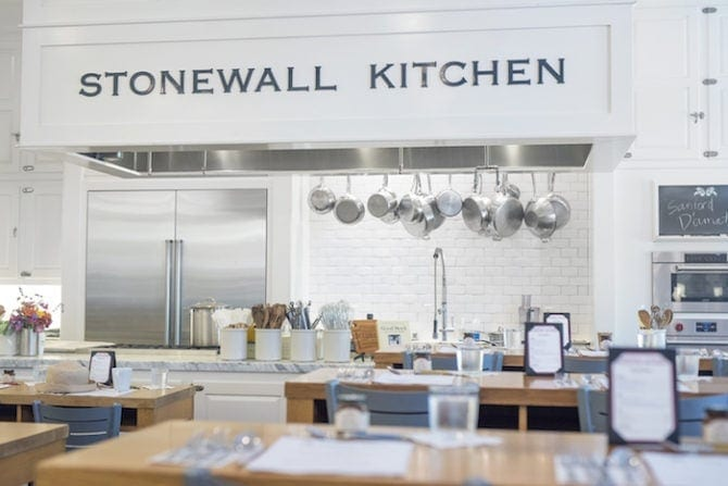 Photo of Stonewall Kitchen-- wooden cooking tables in front of an open kitchen with pots hanging from the ceiling.