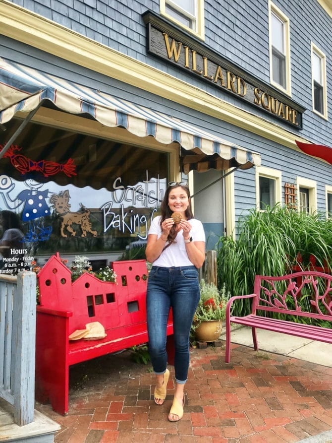 Woman in a t-shirt and jeans standing outside of a bake shop holding a cookie.