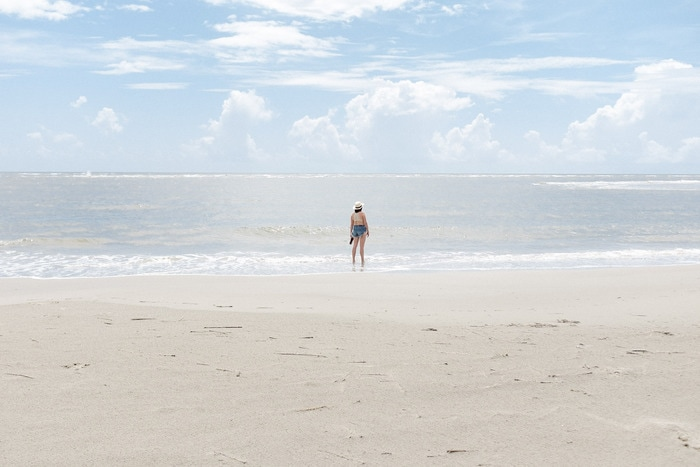 Woman in jean shorts and a hat standing in the surf of the ocean, on a beach in Charleston, SC. Sky is blue with a few light clouds.