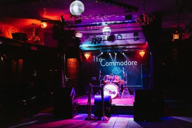 The Commodore, a night spot with a band stage and purple and red lighting.