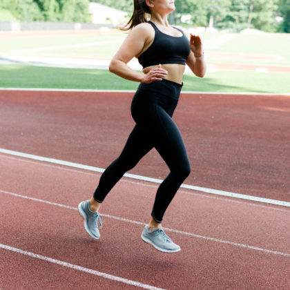 Women running on track with black running tights and black sports bra.