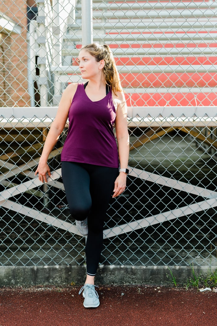 Woman standing against a chainlink finch in front of bleachers wearing Athleta running clothing.