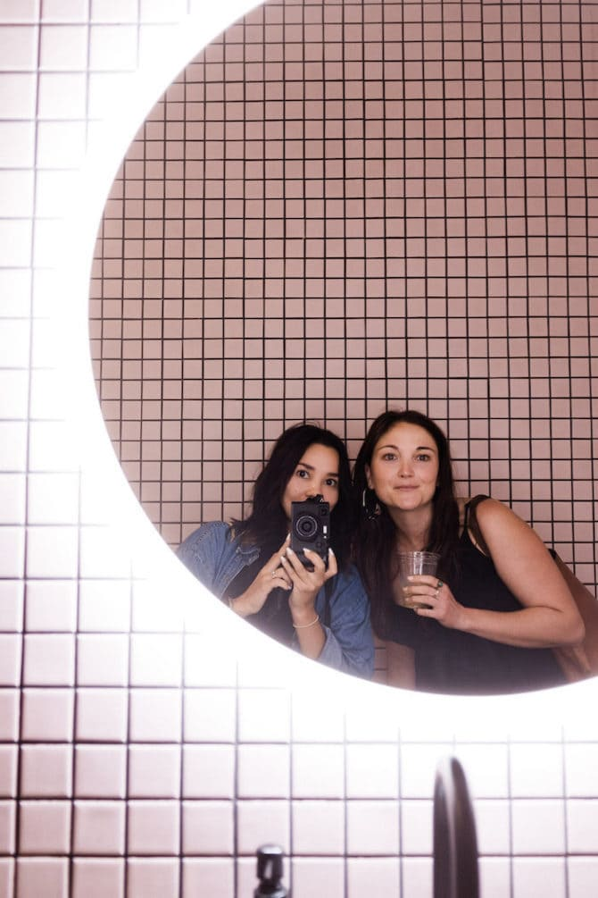 Two women taking a mirror selfie. Mirror is round and surrounded by light. The wall is pink and tiled.