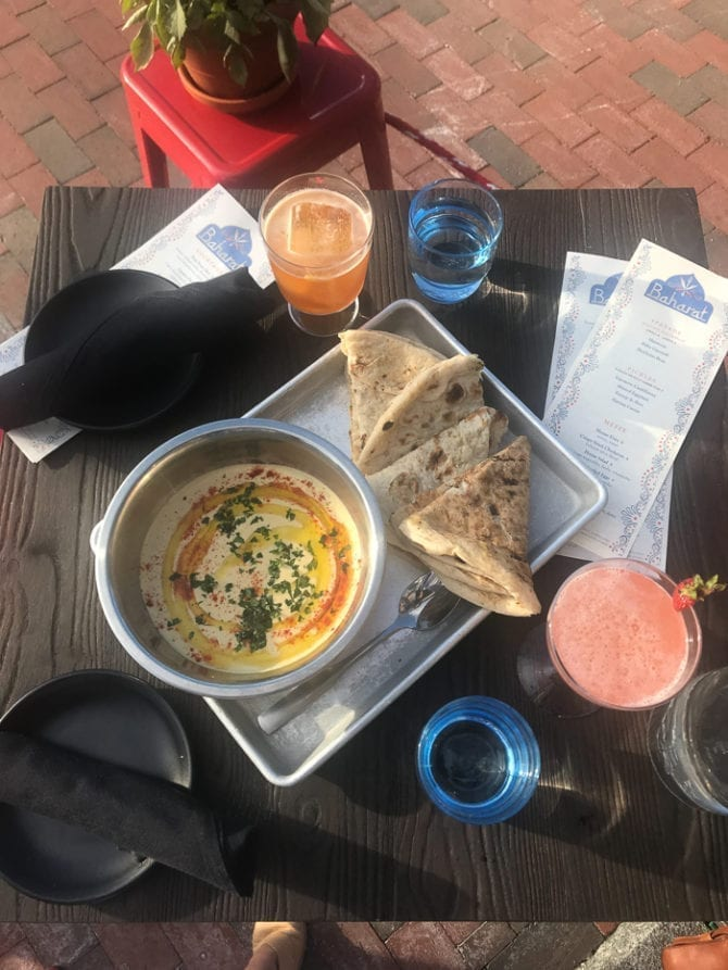 Table with drinks, water, and a plate of hummus and fresh pita bread.