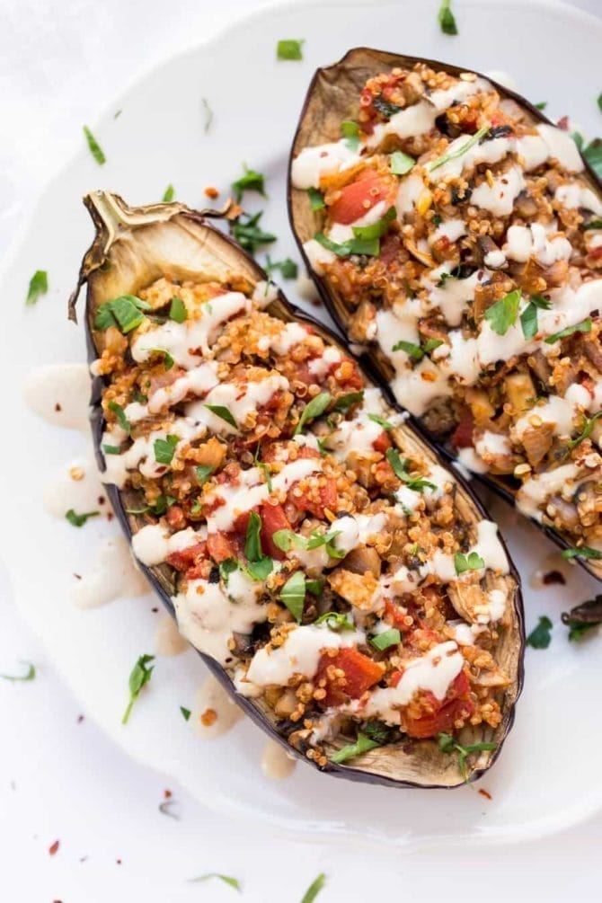 Quinoa Stuffed Eggplant with Tahini Sauce on a plate. (2 eggplant halves)