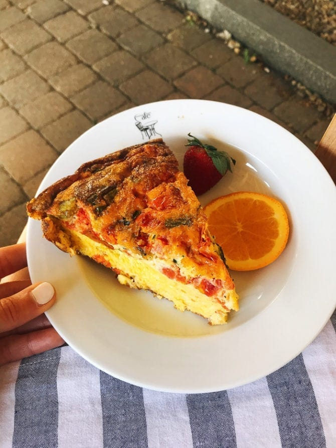 Woman's hand holding a plate with a slice of quiche with peppers, green veggies and cheese. A slice of orange and a strawberry are on the plate.
