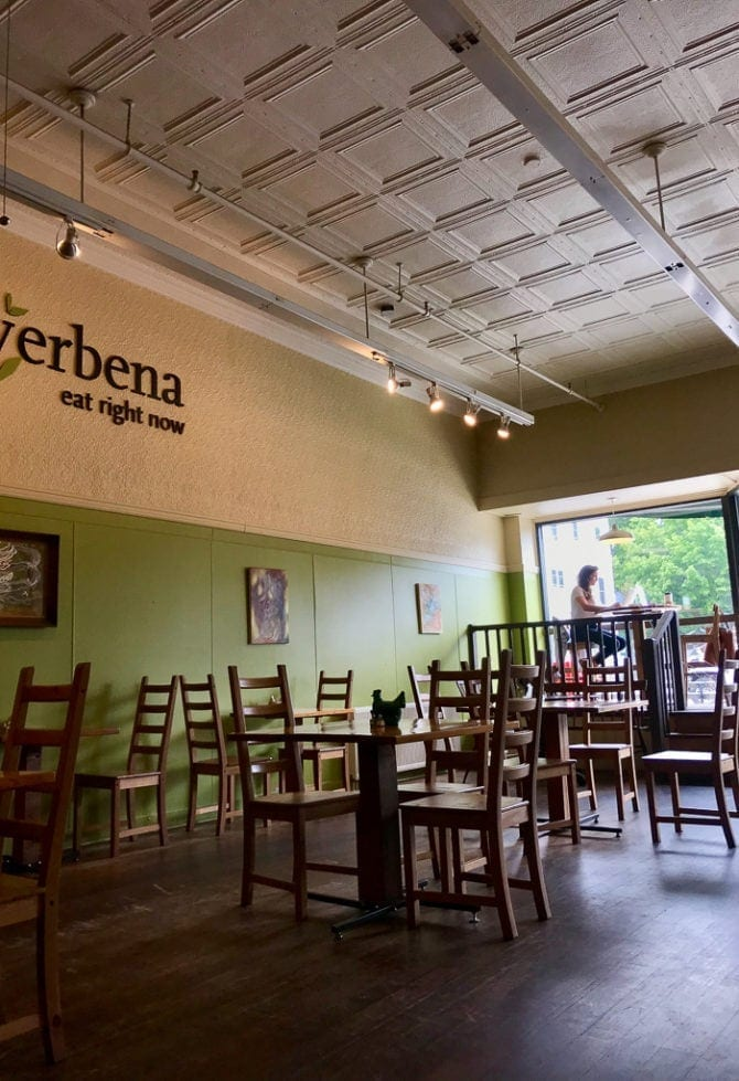 """Inside of a restaurant with wooden tables and chairs, an antique metal ceiling and """"verbena, eat right now"""" on the wall."""