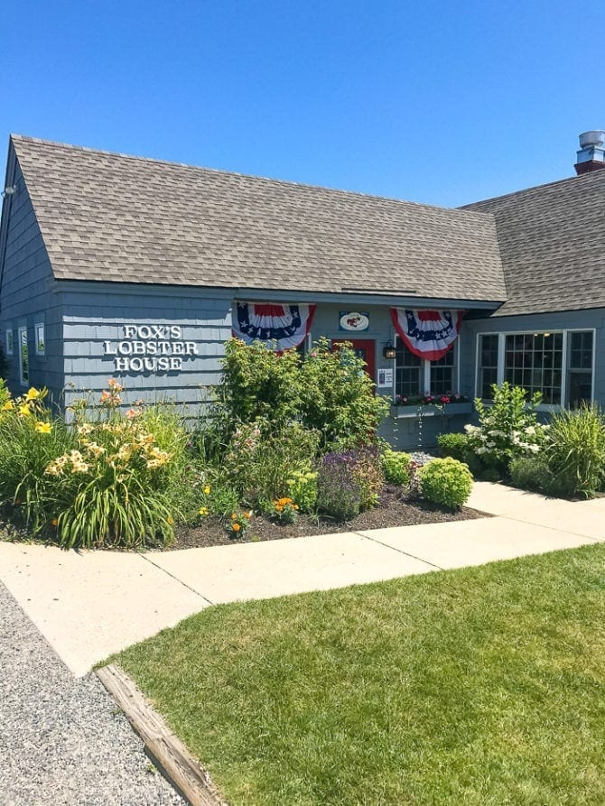 Photo of Fox's Lobster House, a wood shingled restaurant with a grassy lawn, garden, and American flag banners.