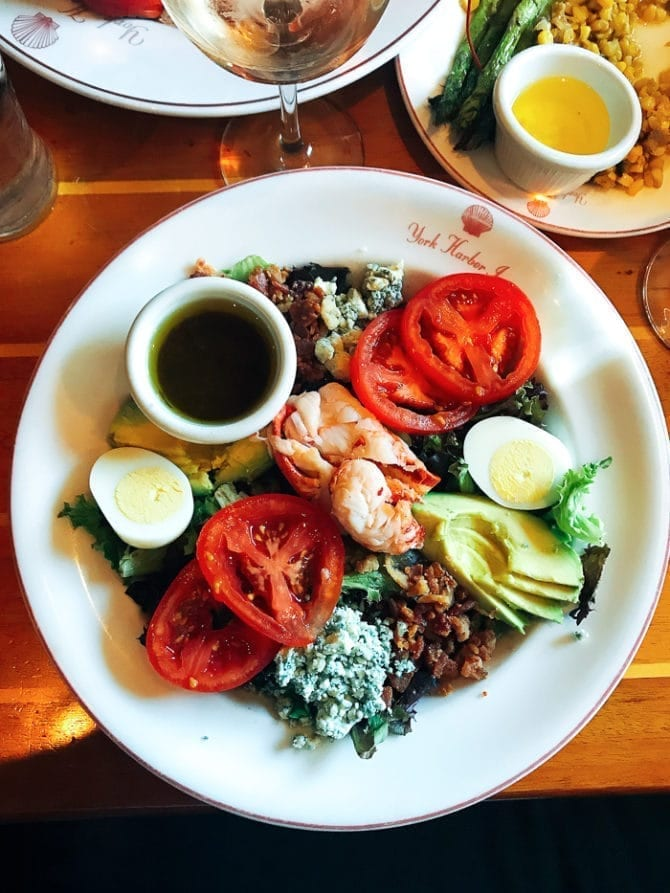Plate on a restaurent table. It is a lobster Cobb salad topped with lobster, avocado, bacon, cheese, egg, tomato, and vinaigrette.