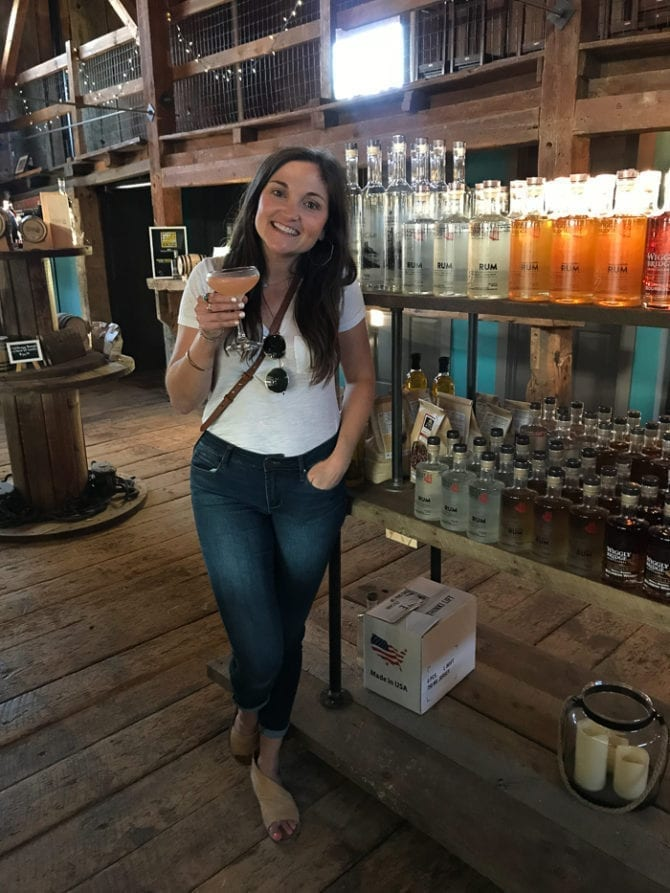 A woman in a t-shirt and jeans posting with her cocktail in front of liquor shelves in a distillery. The floors and walls are wooden.