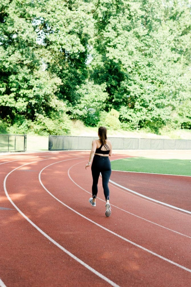 Woman running on track with black tights and sports bra. Photo taken from behind.