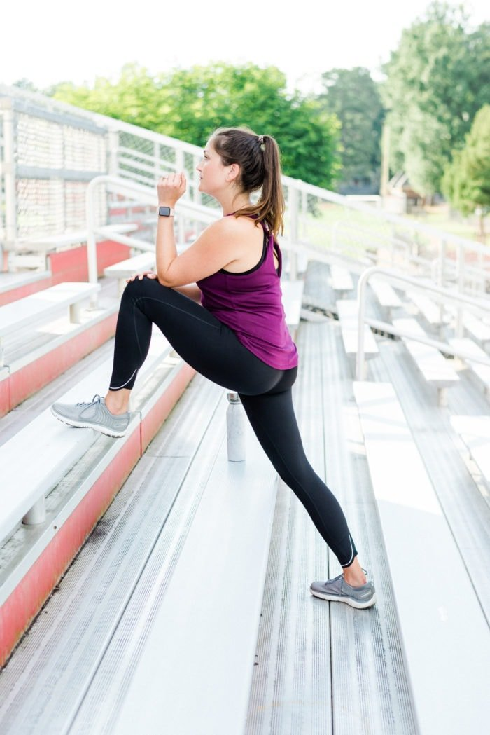 Woman stretching on bleachers in workout attire.
