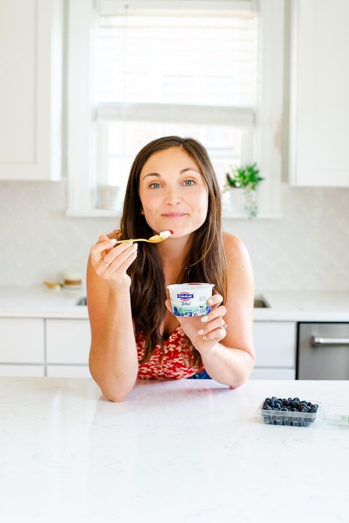 Woman leaning on a kitchen counter eating a cup of Fage blueberry yogurt. A container of blueberries is on the counter.