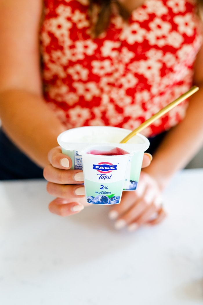 Close up of a woman holding a Fage blueberry yogurt container.